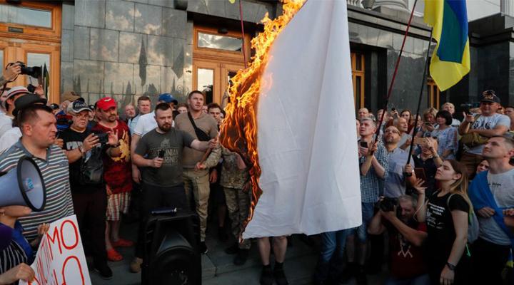 демонстранты сжигают белый флаг
